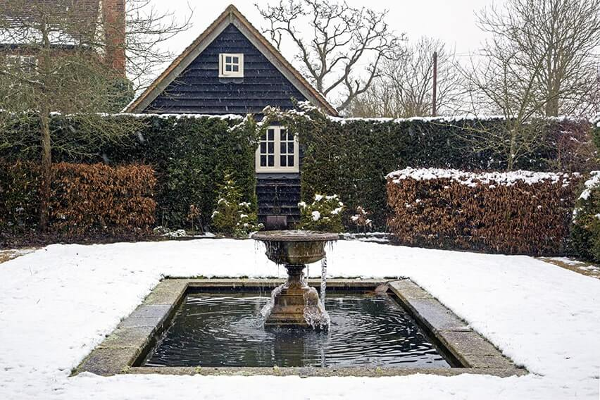 01059043-Taxus-Fagus-hedge-pond-water-fountain-winter-cottage-garden-snow